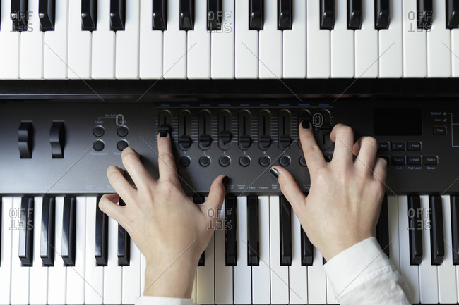 Close-up of pianist playing piano at home