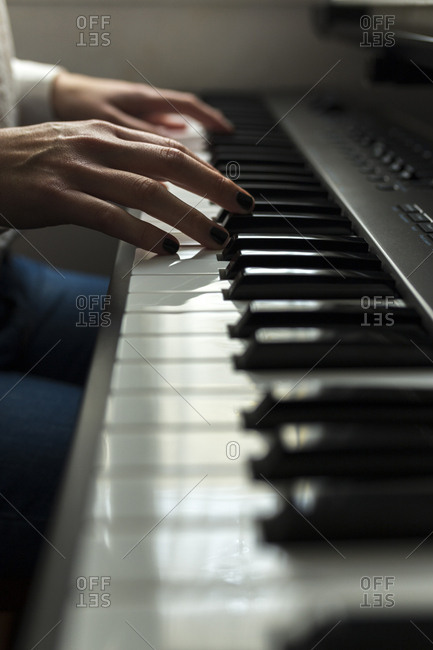Cropped hands of pianist practicing piano at home