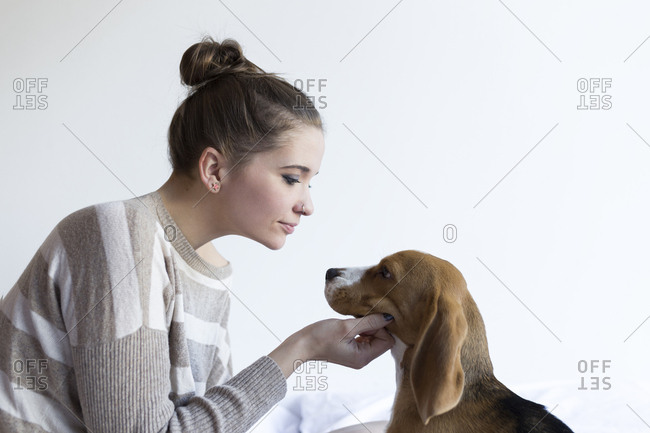 Woman petting beagle against wall in bedroom