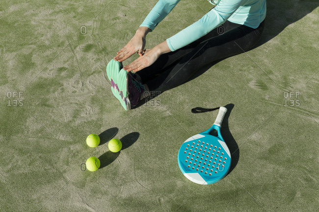 Low section of woman stretching with tennis racket and balls on court during sunny day