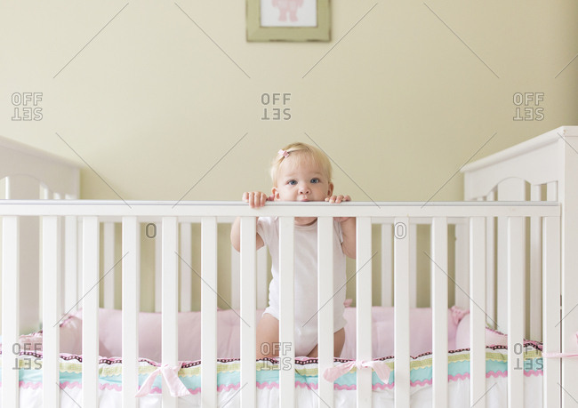Portrait of cute baby girl standing in crib against wall