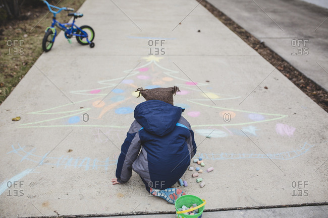 Rear view of boy in warm clothing drawing Christmas tree with chalks on footpath