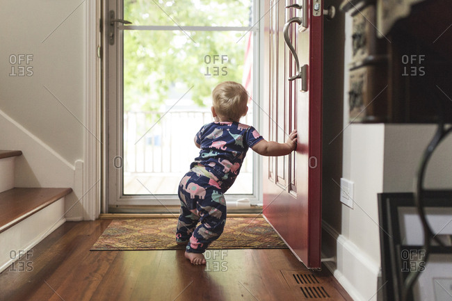 Baby girl standing at doorway