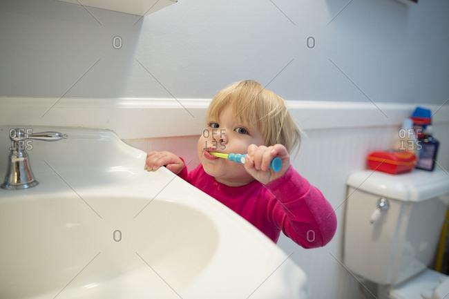 Portrait of girl brushing teeth by bathroom sink at home