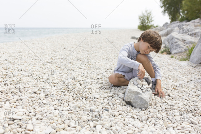 Carefree boy playing with pebbles at lakeshore