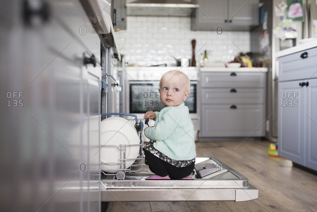 Cute girl looking away while sitting in dishwasher at kitchen