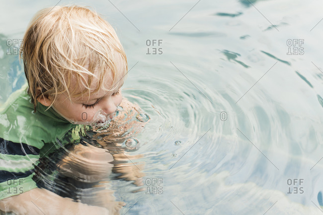 High angle view of playful boy blowing bubbles in water