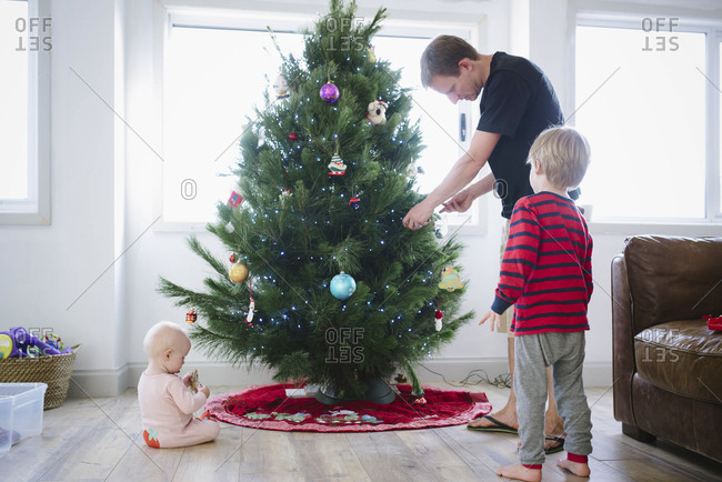 Father decorating Christmas tree while standing with children at home