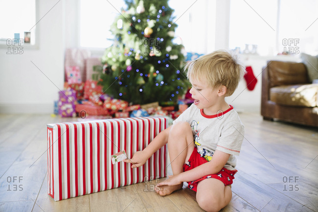 Cute boy with Christmas present sitting on hardwood floor at home