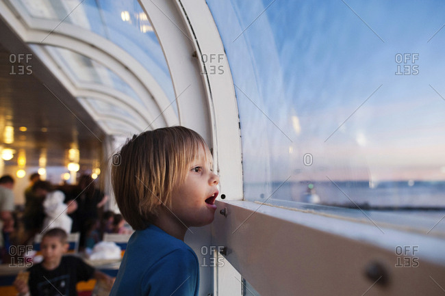 Side view of girl looking through window while traveling in cruise ship