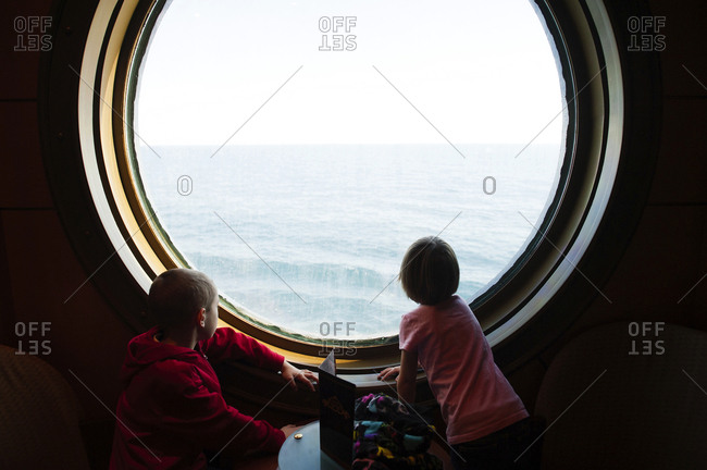 Siblings looking at sea while standing by porthole in cruise ship