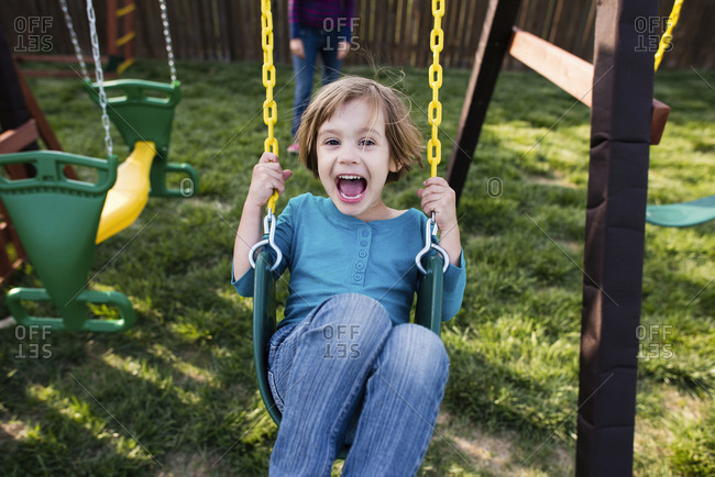 Portrait of happy girl swinging at playground with mother in background