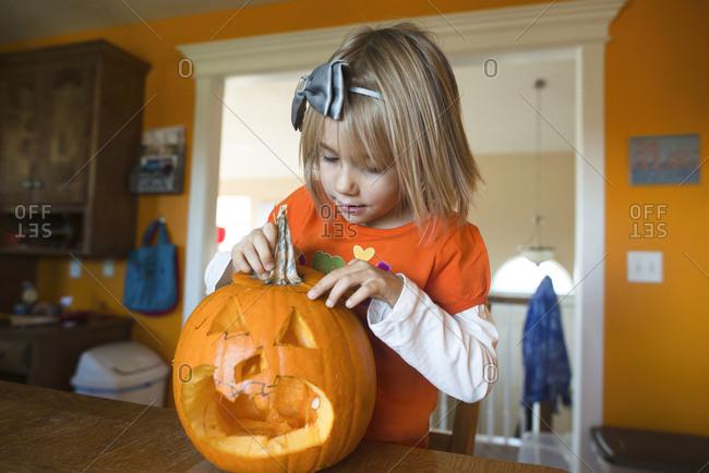 Girl making Jack O' Lantern at home