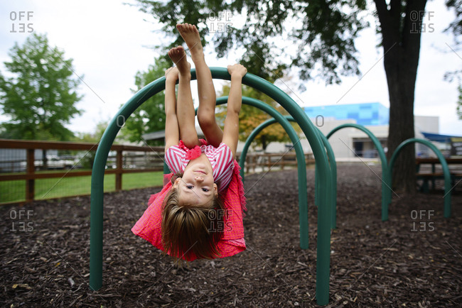 Portrait of girl hanging upside down on outdoor play equipment at playground