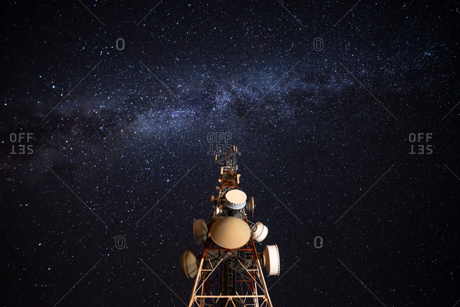 From below wonderful view of media antenna and silhouettes of electricity high voltage power towers against night city on horizon and gorgeous Milky Way in clear sky