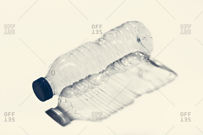Side view of empty plastic bottle with blue cap with contrast shadow on white surface