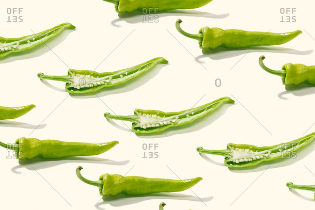 From above creative composition of sliced green pepper with seeds among whole peppers on white surface