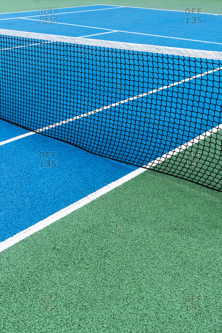 Detail of a blue yennis court with black net on Outdoor