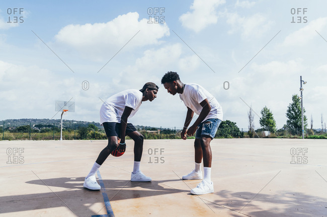 Side view of African American guys playing basketball in bright day on play ground