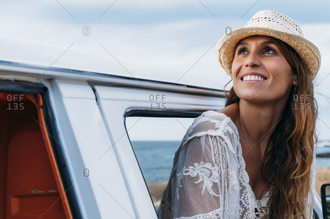 Pleasant charming lady in hat looking away with smile while opening door of car on beach
