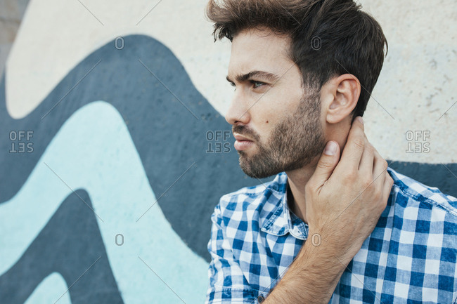 Cheerful young male in casual plaid shirt looking away with painted wall on background