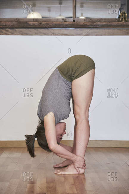 Side view of barefoot female in sportswear performing forward bend while practicing yoga in studio