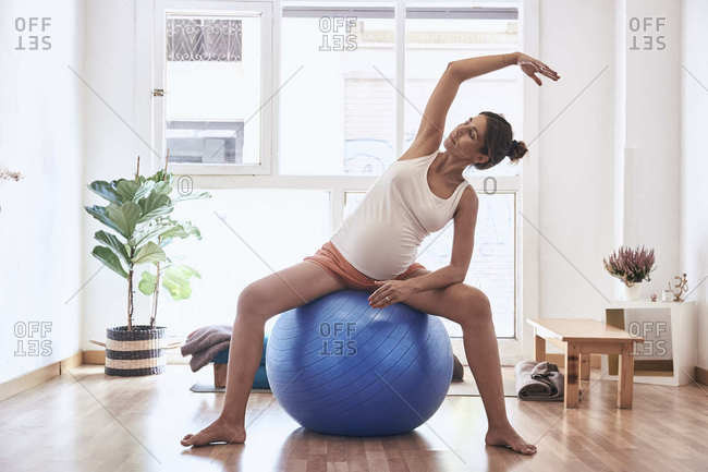 Relaxed pregnant female stretching on blue exercise ball during yoga workout in studio