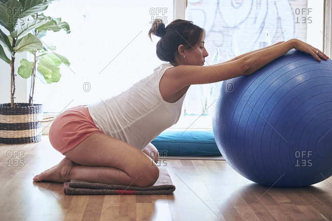 Side view of barefoot pregnant lady sitting on blanket and stretching back near exercise ball while doing yoga in light studio