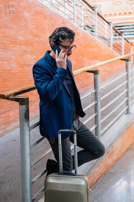 Aged man standing with baggage and talking on smartphone
