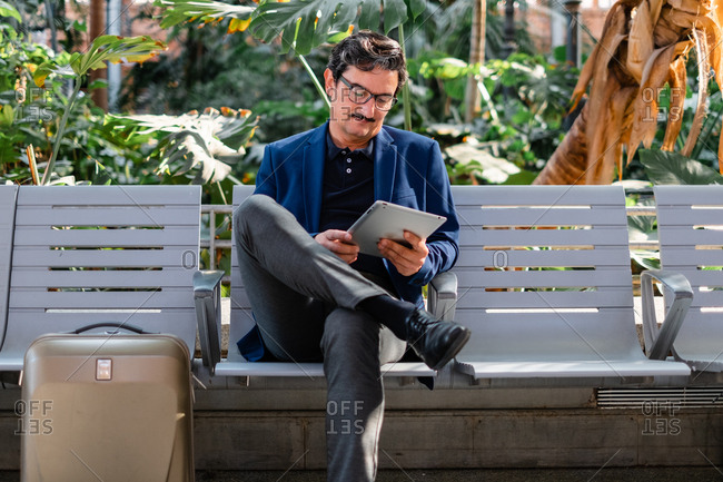 Aged handsome man using digital tablet outdoors