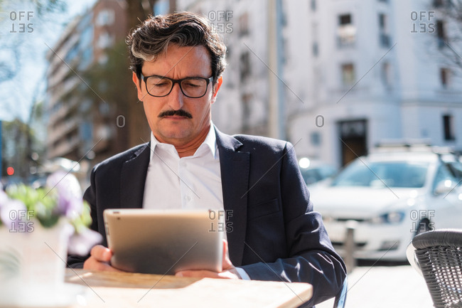 Elderly man using gadget while relaxing at cafe