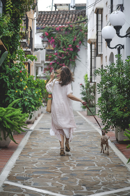 Back view of female in casual summer dress with bag walking down in Marbella street with Italian Greyhound dog on leash