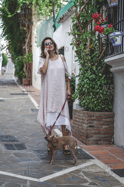 Optimistic joyful trendy happy woman walking on narrow street in Marbella holding greyhound dog on leash while speaking on the mobile phone