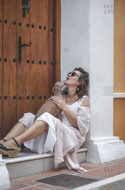 Side view of smiling stylish content woman in summer dress holding a small dog while sitting at a door step together