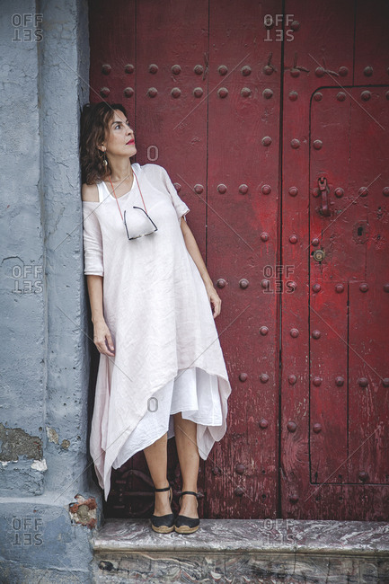 Thoughtful pensive serious dreaming stylish female in summer dress leaning on wall near ancient maroon door in town looking away