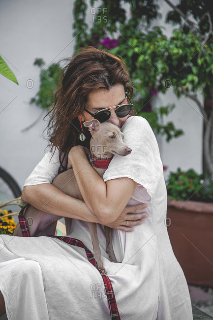 Side view of happy calm female cuddling and kissing small dog while resting together on stone fence of flowerbed with tropical plants in Marbella