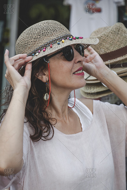 Side view of confident focused serious female trying straw hat on during shopping on urban clothing market in Marbella