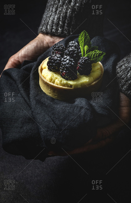 Unrecognizable cropped person hands holding a homemade small cake with blackberry and delicious cream of vanilla and mint on dark background