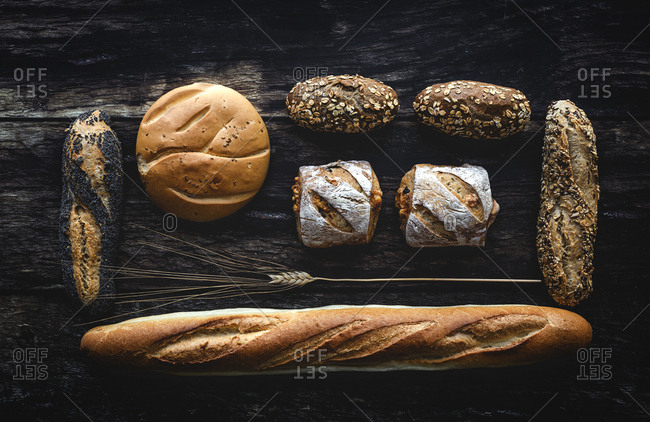 Gold assortment bread homemade on dark wood background, captured from above top view, flat lay in knolling concept