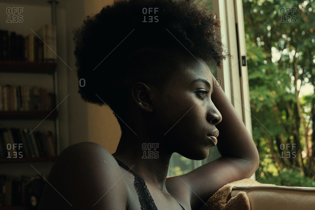 Side view of African American mysterious disappointed resentful sad woman looking out windows