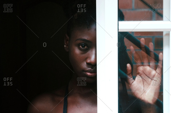 Portrait of African American mysterious disappointed resentful sad woman looking out window frame half from shade and touching glass with palm