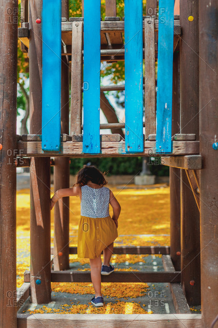 Back view of active child climbing in blue and brown wooden construction in playground