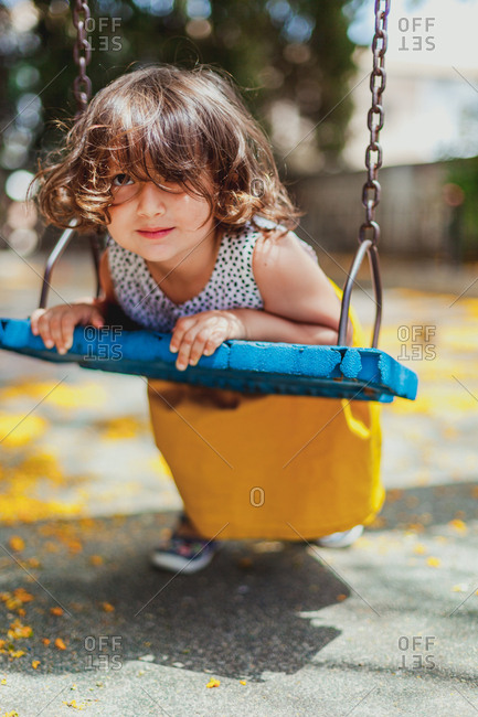 Little girl riding swing in bright day on playground