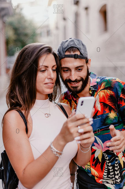 Trendy ethnic man and woman sharing mobile phone checking photos while standing on street