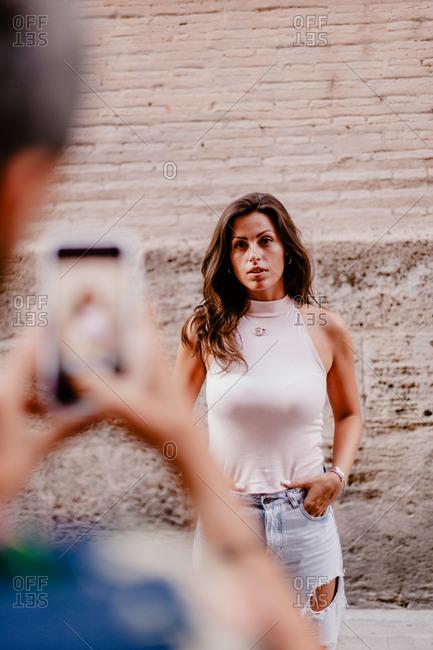 Faceless male taking photo of brunette woman