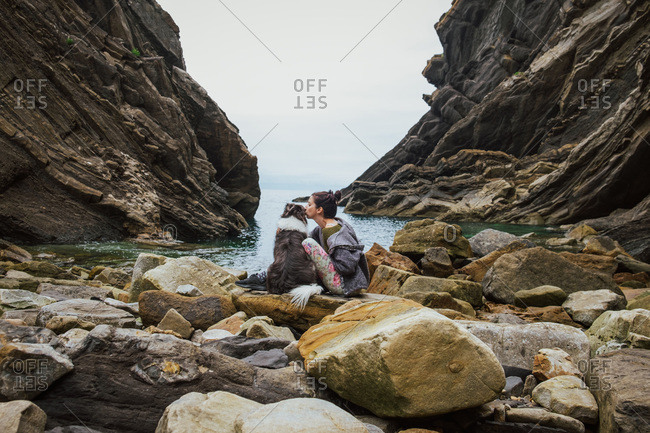 Side view of female in casual clothes sitting beside Border Collie and kissing dog on rocky shore against gorge and tranquil bay water under cloudy sky