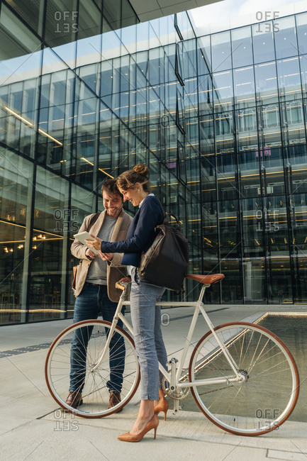Cheerful man and woman with bicycle smiling and looking at a tablet while communicating outside office building on modern city street