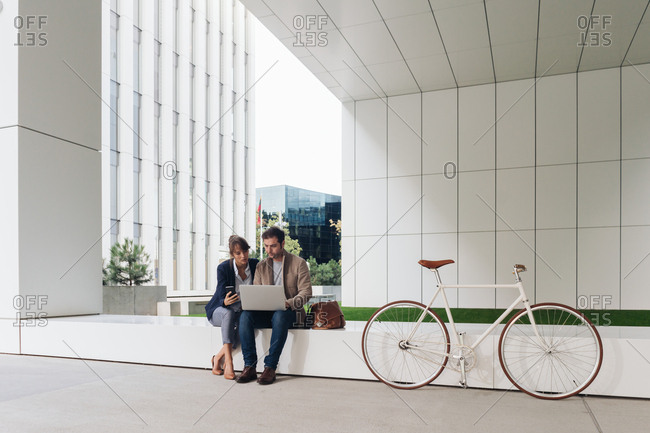 Delighted businesspeople smiling and browsing laptop together while sitting outside modern building near bicycle on city street