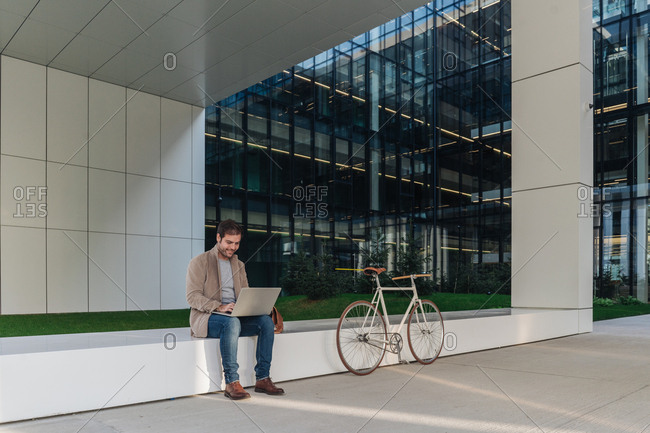 Full body happy man manager smiling and browsing laptop while sitting outside near bicycle on a contemporary building on city street