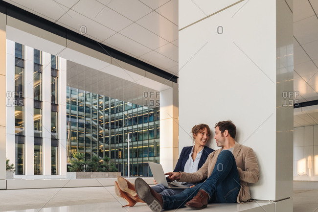Delighted businesspeople smiling and browsing laptop together while sitting outside modern building on city street